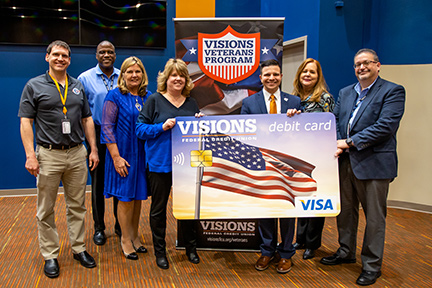 Visions FCU and Operation Homefront staff holding an enlarged version of the Americana debit card design