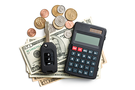 calculator and car keys on top of some money