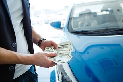 man holding money next to a blue car