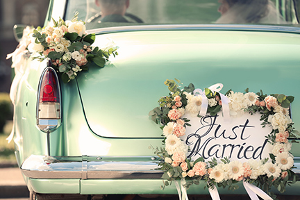 """vintage car with """"just married"""" sign on the back surrounded by white and pink flowers"""